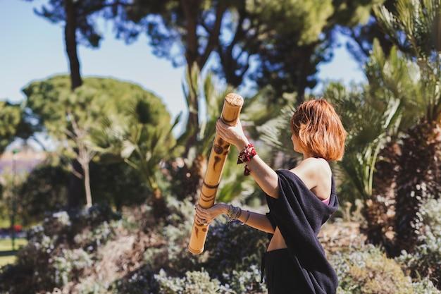 Seitenansichtfrau, die mit bambusstock trainiert