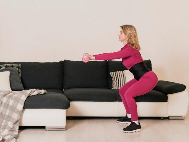 Seitenansichtfrau, die mit gewichten ausarbeitet