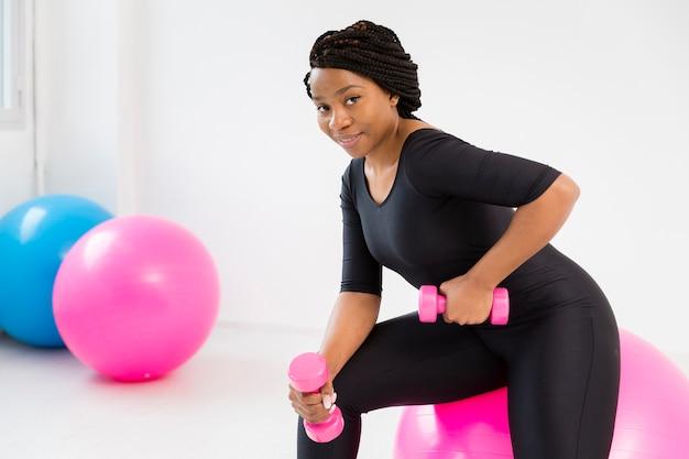 Seitenansichtfrau, die mit handgewichten arbeitet