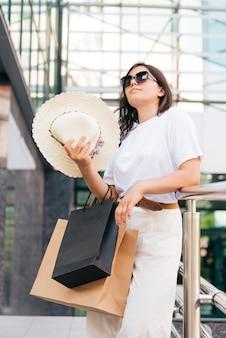 Seitenansichtfrau, die nach dem einkauf abkühlt