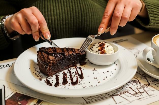 Seitenansichtfrau, die schokoladenkuchen mit eiscreme und schokoladenglasur auf einem teller isst