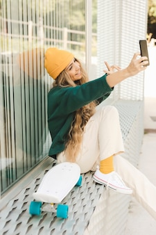 Seitenansichtfrau, die selfie mit skateboard nimmt