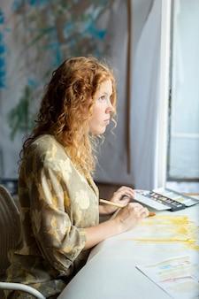 Seitenansichtfrau, die zuhause malt