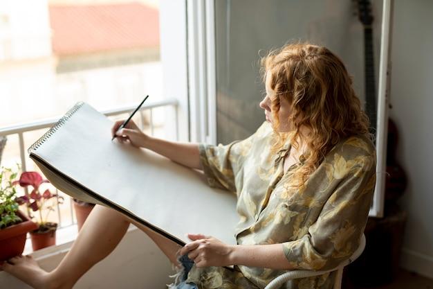 Seitenansichtfrau, die zuhause zeichnet