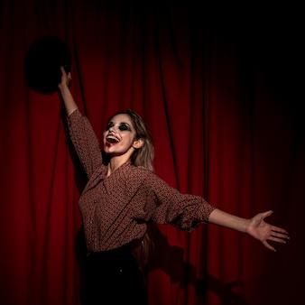 Seitenansichtfrau gekleidet als clown, der glücklich ist