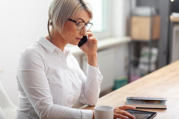 Seitenansichtfrau im büro sprechend über telefon