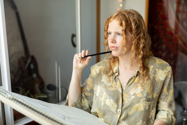 Seitenansichtfrau mit dem bleistiftdenken