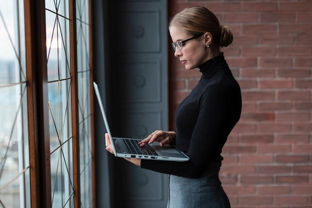Seitenansichtfrau mit der formellen kleidung, die an laptop arbeitet