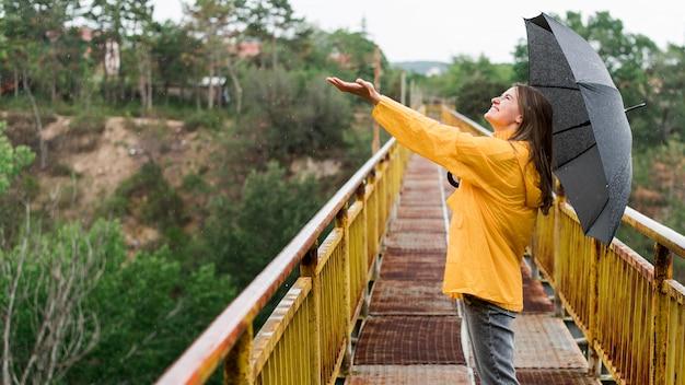 Seitenansichtfrau mit schwarzem regenschirm, der ihre hand erhebt