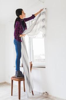 Seitenansichtfrau mit vorhang