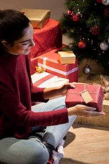 Seitenansichtfrau, welche die geschenke sie eingewickelt bewundert