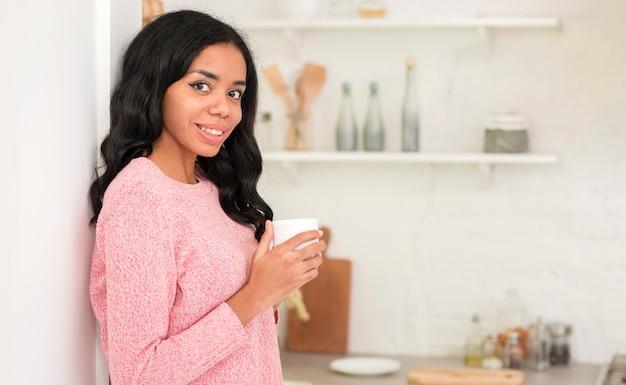 Seitenansichtfrau zu hause, die kaffee trinkt