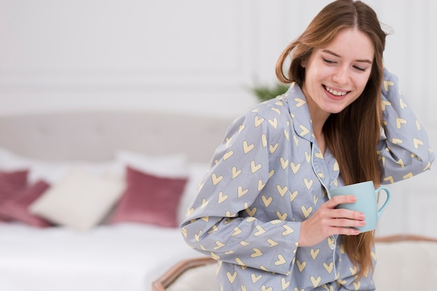 Seitenansichtfrau zu hause, die tee trinkt