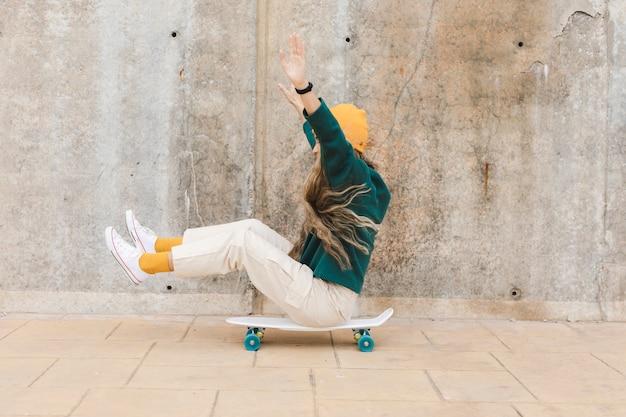 Seitenansichtfrauen-reitskateboard