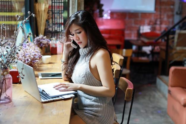 Seitenansichtgeschäft, das online, junge asiatische frau im freizeitkleid arbeitet an computer verkauft