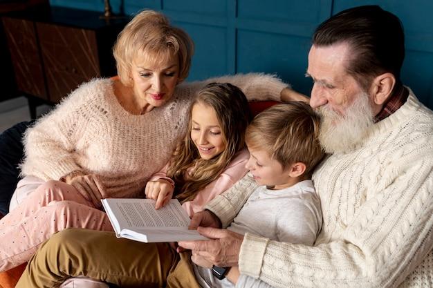 Seitenansichtgroßeltern, die ein buch mit ihren enkelkindern lesen