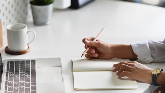 Seitenansichthände, die auf notizbuchpapier, geerntete schussfrau arbeitet an tabelle schreiben.