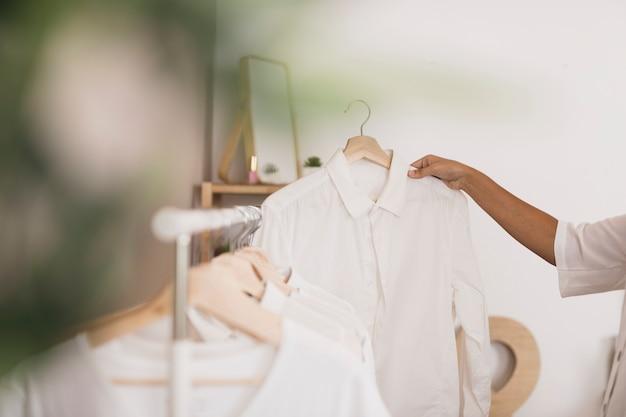 Seitenansichthand, die ein weißes hemd wählt