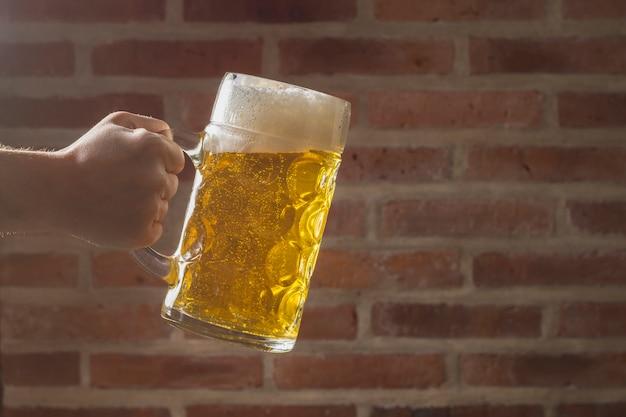 Seitenansichthand mit dem halben liter, das bier isst