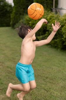 Seitenansichtjunge, der mit ball spielt