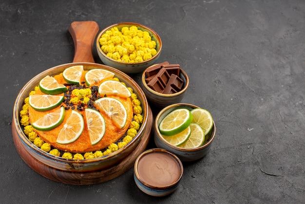 Seitenansichtkuchen und kalkweiße schalen mit gelben bonbons, schokoladenscheiben aus limette und schokoladencreme neben dem appetitlichen orangenkuchen auf dem schwarzen tisch
