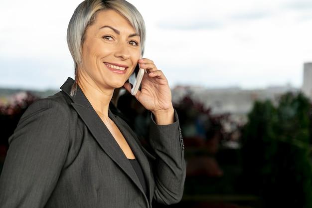 Seitenansichtlächelnfrau, die über telefon spricht