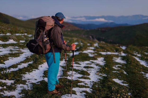 Seitenansichtmann, der auf dem feld mit schneeresten mit dem wandern des rucksacks und der stöcke steht