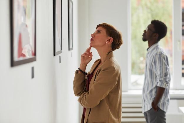 Seitenansichtporträt der eleganten jungen frau, die gemälde beim erkunden der galerieausstellung der modernen kunst betrachtet,