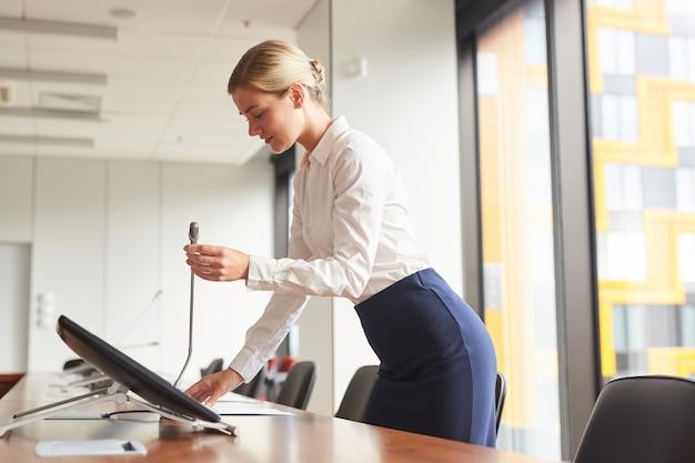 Seitenansichtporträt der eleganten sekretärin, die mikrofon einstellt, während konferenzraum für geschäftsereignis vorbereitet,