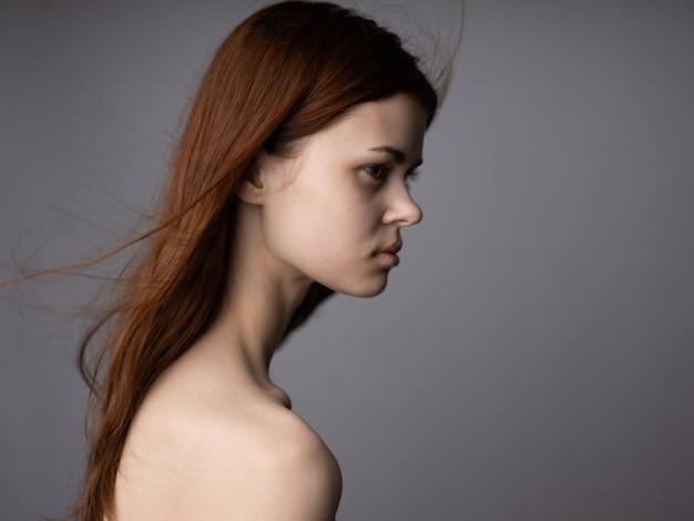 Seitenansichtporträt der frau mit entblößten schultern für grauen hintergrund