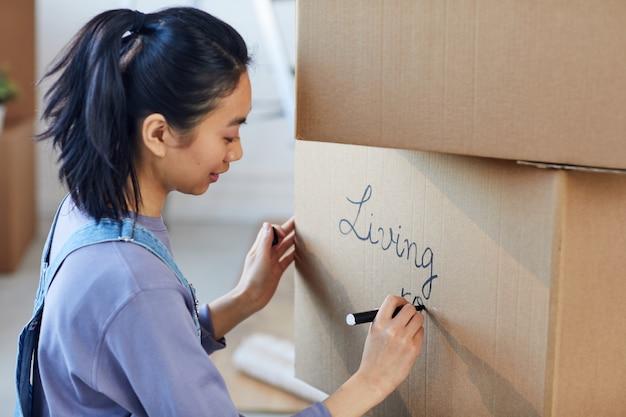 Seitenansichtporträt der lächelnden asiatischen frau, die auf pappkartonbeschriftung für den umzug in ein neues haus schreibt