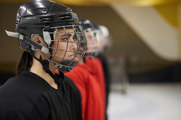 Seitenansichtporträt der weiblichen eishockeymannschaft, die in der linie vor dem spiel auf der eisbahn steht