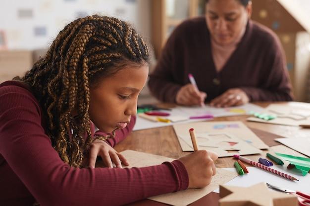 Seitenansichtporträt der zeichnung des jugendlichen afroamerikanischen mädchens beim genießen der kunst- und handwerksklasse in der schule, kopienraum