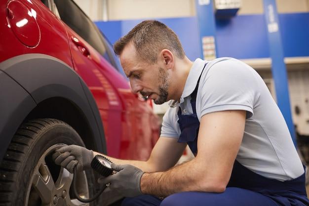Seitenansichtporträt des bärtigen automechanikers, der druck in reifen während der fahrzeuginspektion im garagengeschäft prüft, kopienraum