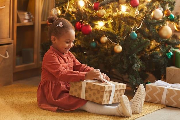 Seitenansichtporträt des glücklichen afroamerikanischen mädchens, das weihnachtsgeschenke beim sitzen am baum zu hause, kopienraum öffnet
