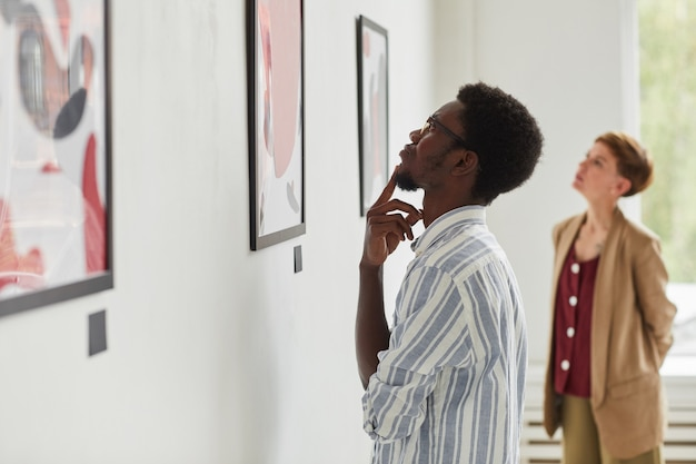 Seitenansichtporträt des jungen afroamerikanischen mannes, der gemälde beim erkunden der galerieausstellung der modernen kunst betrachtet