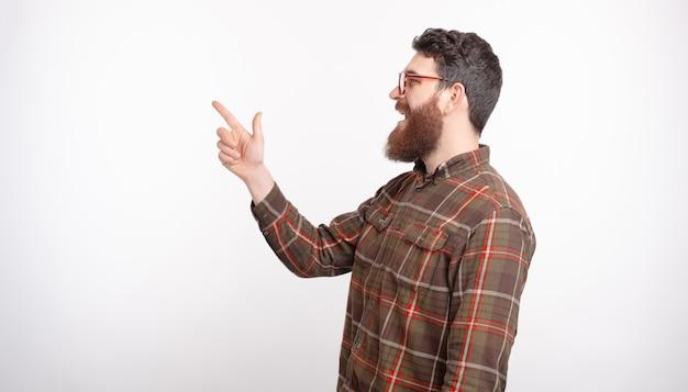 Seitenansichtporträt des jungen bärtigen kerls, der auf copyspace über weißem hintergrund zeigt