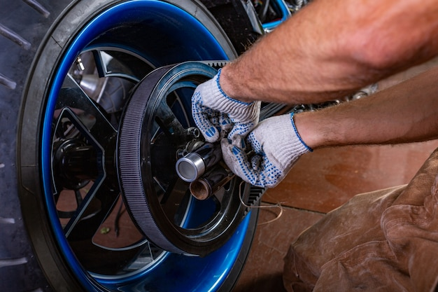 Seitenansichtporträt des mannes arbeitend in der garage, die motorrad repariert. hände hautnah
