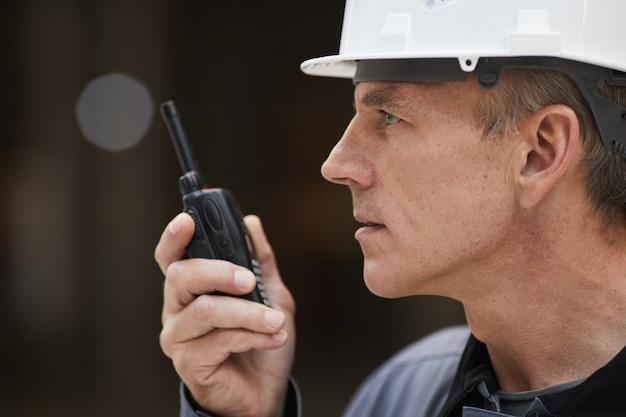 Seitenansichtporträt des reifen arbeiters, der durch walkie-talkie spricht, während arbeit auf der baustelle oder in der industriewerkstatt überwacht