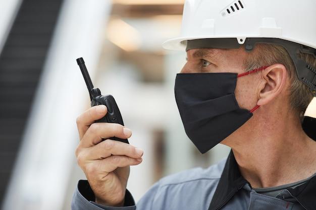 Seitenansichtporträt des reifen arbeiters, der maske trägt und durch walkie-talkie spricht, während auf industriestandort arbeitet,