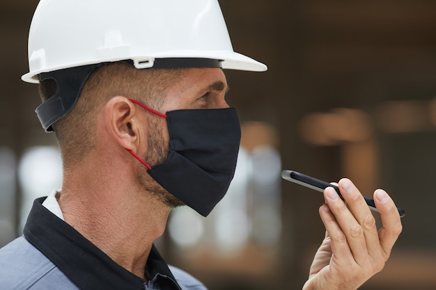 Seitenansichtporträt des reifen arbeiters, der maske trägt und sprachnachricht während der arbeit am industriestandort aufzeichnet,