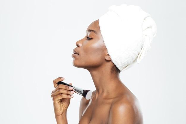 Seitenansichtporträt einer afroamerikanischen frau, die make-up mit dem pinsel auf einem weißen hintergrund aufträgt