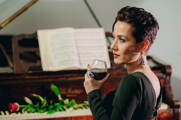 Seitenansichtporträt einer attraktiven und eleganten frau, die am klavier sitzt und weinglas rote rose auf der klaviertastatur hält