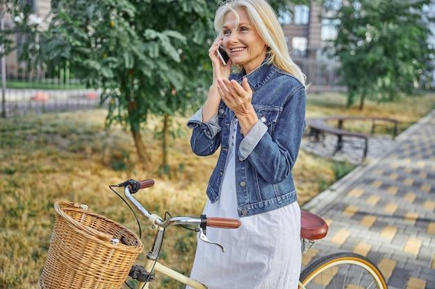 Seitenansichtporträt einer glücklich lächelnden frau mit retro-fahrrad, die auf dem smartphone in der stadtstraße spricht