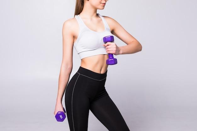 Seitenansichtporträt einer hübschen jungen sportlerin, die übungen mit hanteln lokalisiert auf einer weißen wand tut