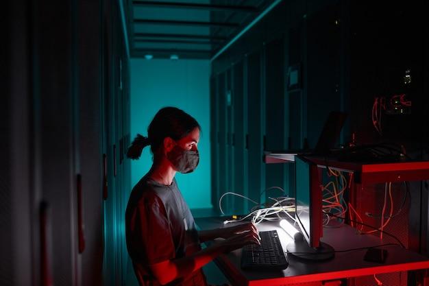 Seitenansichtporträt einer it-ingenieurin, die eine maske trägt, während sie den computer benutzt und im serverraum arbeitet, der von rotem licht beleuchtet wird, kopierraum