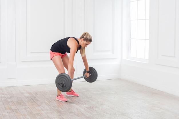 Seitenansichtporträt einer jungen athletischen, schönen bodybuilderin in rosa shorts und schwarzem oberteil, die falsche kniebeugen macht und im fitnessstudio mit der langhantel an der weißen wand trainiert. indoor, studioaufnahme,