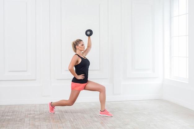 Seitenansichtporträt einer jungen sportlichen, schönen bodybuilderin in rosa shorts und schwarzem oberteil, die hanteln über dem kopf hält und kniebeugen mit einem bein im fitnessstudio an der weißen wand macht. indoor, studioaufnahme