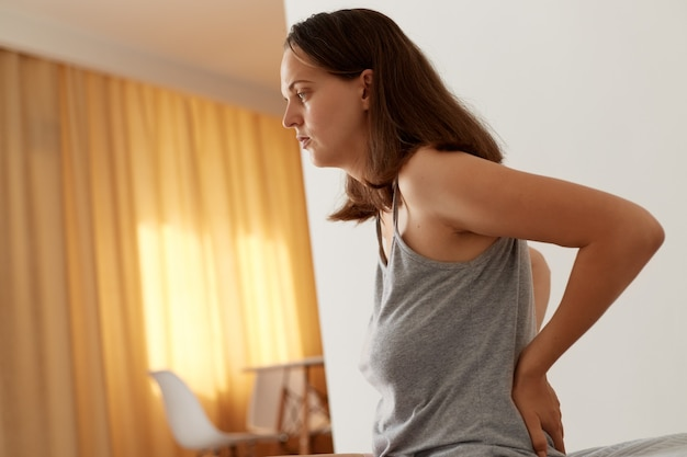 Seitenansichtporträt einer kranken frau, die freizeitkleidung trägt, die auf dem bett sitzt, ihren rücken berührt, an nierenschmerzen leidet, gesundheitliche probleme hat, behandelt werden muss.