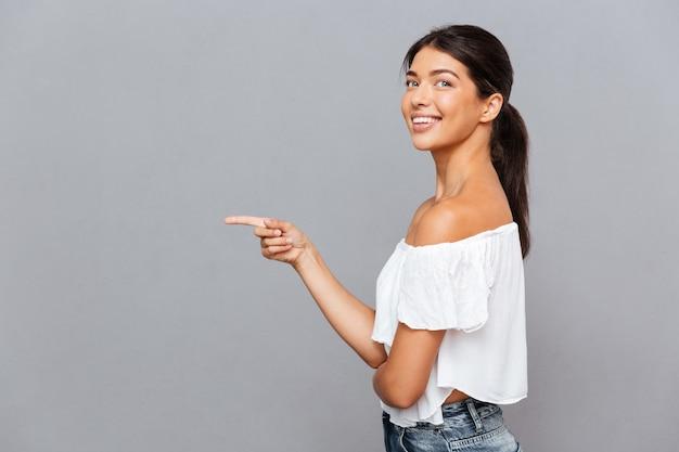 Seitenansichtporträt einer lächelnden jungen frau, die den finger beiseite lokalisiert auf der grauen wand zeigt